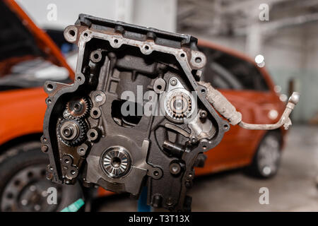 Selective focus. Engine Block on a repair stand with Piston and Connecting Rod of Automotive technology. Blurred car on background. Interior of a car - Stock Photo