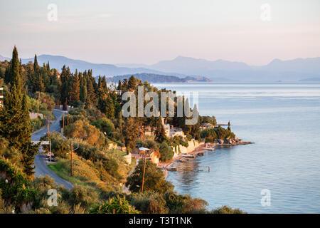 Summer sunrise on coast, Corfu island, Greece. View of the coast, the capital of the island and Albanian mountains. - Stock Photo