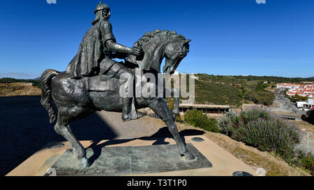 Equestrian bronze statue of moorish soldier overlooking village - Stock Photo