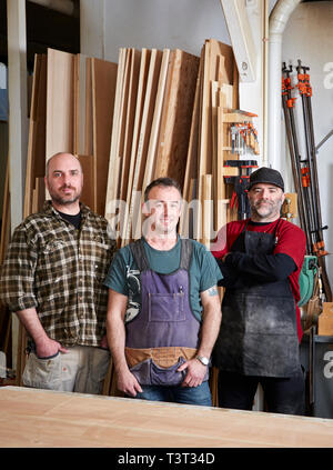 Carpenters smiling in workshop - Stock Photo