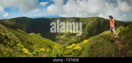 Hiker walking on hilltop dirt path over Cabeco Gordo crater, Faial, Portugal - Stock Photo