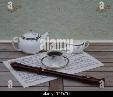 English teacup with saucer, teapot and cream jug, fine bone china porcelain, and a block flute on a sheet of music - Stock Photo