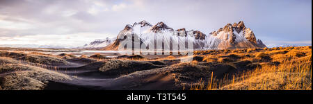 Panoramic view of mountains over remote fields - Stock Photo