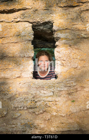 Portrait of a 12 year old girl with brown hair looking at camera through a hole in a stone wall. - Stock Photo
