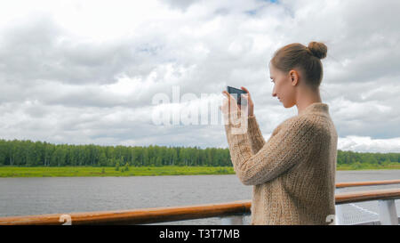 Woman taking photo of landscape with smartphone on deck of cruise ship - Stock Photo