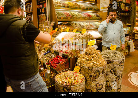 Istanbul, Turkey, March 07, 2019: seller talking on phone and buyer at store selling traditional tea inside of Egyptian Bazaar, Istanbul - Stock Photo
