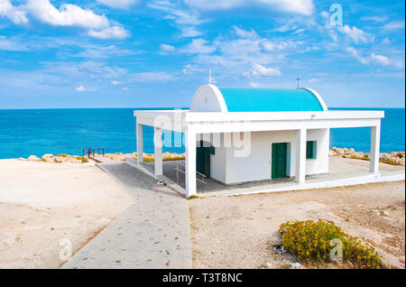 White Agioi Anargyroi Chapel with green doors near Cape Greco, Cyprus. A stone path leading to deep blue azure water, cats lying in the shade. Amazing - Stock Photo