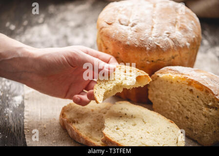Women's hands breaking homemade natural fresh bread with a Golden crust on a napkin on an old wooden background. Concept of baking bakery products - Stock Photo