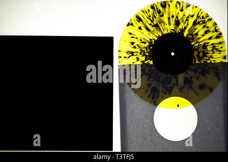 A unique yellow coloured vinyl record on a light box. - Stock Photo