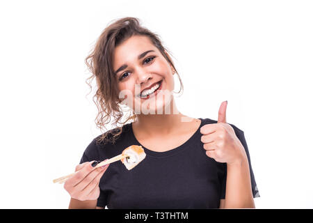 Cheerful young woman eating sushi with chopsticks isolated over white background, thumbs up - Stock Photo