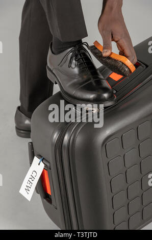 Airline pilot brushing his black uniform shoes. - Stock Photo
