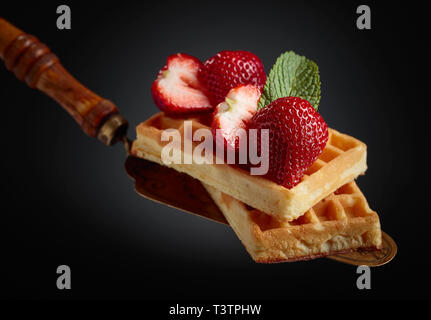 Belgian waffles with strawberries and mint on a black background. - Stock Photo