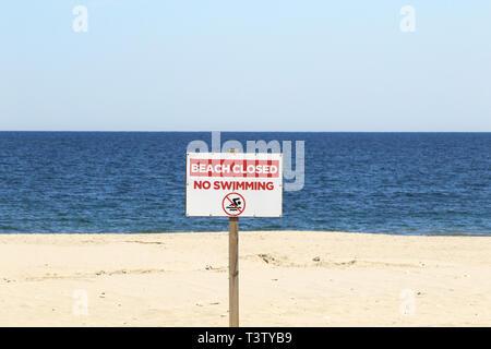 An off season sign warning beach closed no swimming. point Pleasant Beach, New Jersey, USA Stock Photo