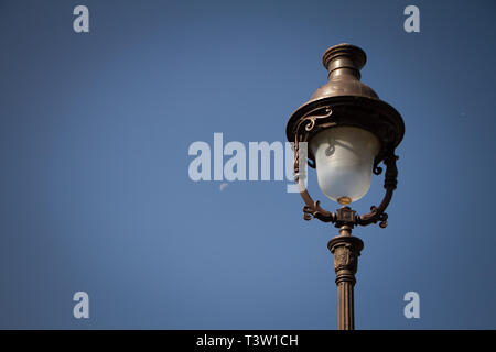 Vintage lantern on the background of a clear blue sky and a translucent rising moon, Paris, Montmartre, light vignette, free space for text. - Stock Photo