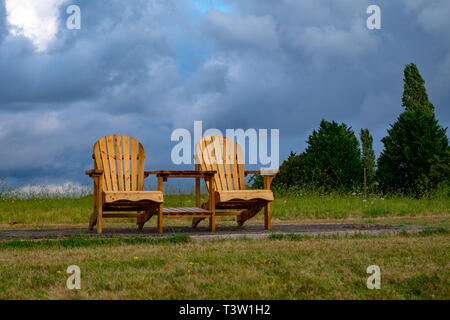 Two sunlit empty chairs stand in an field under a moody, cloudy sky denoting emotions such as loneliness. The scene is in central France - Stock Photo