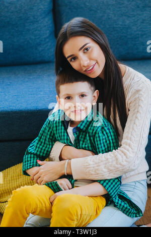 Portrait of a mother with her little son at home. Tenderness, love, multinational family - Stock Photo