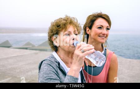 Senior sportswoman drinking water with female coach - Stock Photo