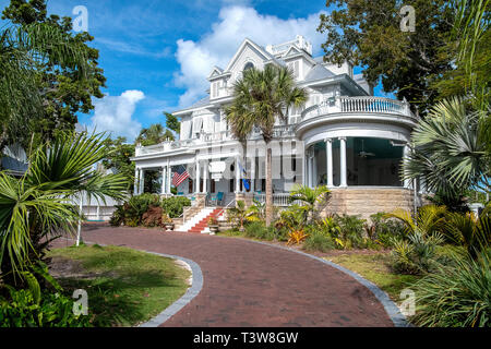 vintage white mansion in Key West Florida with curved brick driveway and palm trees