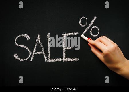 woman's hand writing on the blackboard the word sale - Stock Photo