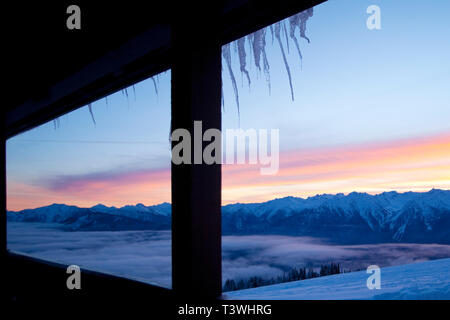 Colorful sky over snow covered mountains in remote landscape - Stock Photo