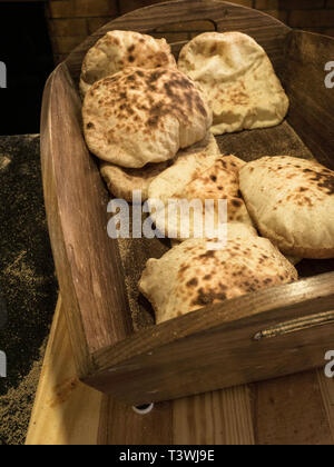 homemade wholegrain pita bread on wooden basket, Traditional and typical food of Arabic cuisine - Stock Photo