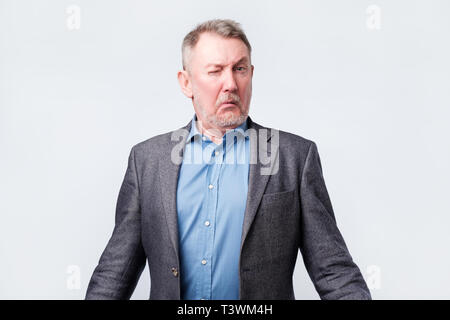 Doubtful senior man in jacket is confused - Stock Photo
