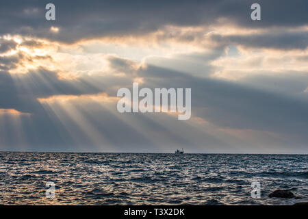 Mousehole, Cornwall, UK. 12th Apr, 2019. UK Weather. The sun made brief appearance though the clouds this morning, bringing some spectular crespicular rays over the sea at Mounts Bay Credit: Simon Maycock/Alamy Live News - Stock Photo
