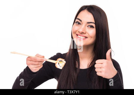 Cheerful young asian woman eating sushi with chopsticks isolated over white background, thumbs up - Stock Photo