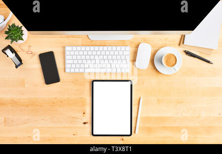 Top view of wooden office desk with tablet, pencil, large desktop computer, keyboard, mouse, smartphone, notebook, headphone, plant and cup of coffee. - Stock Photo