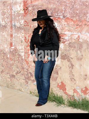 Young cowgirl wearing cowboy boots and a black hat leans up against a wall in a small southwestern town in Arizona. - Stock Photo