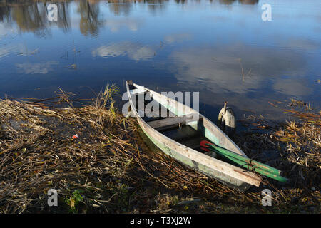 Lonely old wooden fishing boat on lake coast and reflections on water - Stock Photo