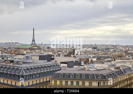Paris rooftops view and Eiffel Tower in a cloudy day in France - Stock Photo