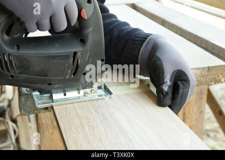 Worker cuts laminate flooring before laying. Man laying laminate flooring in construction, repair concept. - Stock Photo