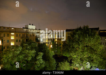 Buildings and green trees at night, illuminated cloudy sky - Stock Photo
