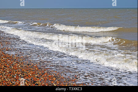 sea view of the sea waves as they splash on the pebble beach along the Kent coast creating white sea spray and foam - Stock Photo