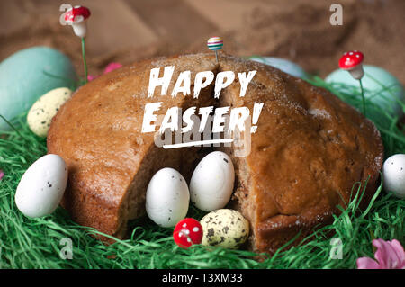 Homemade cake in a nest from fake green grass and Easter eggs isolated on sackcloth texture. Happy Easter Card - Stock Photo