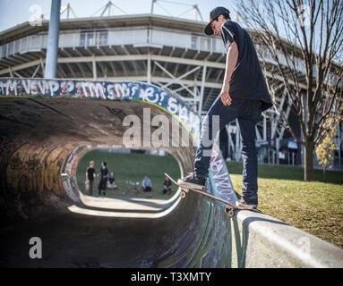 Caucasian man skating on half pipe at skate park - Stock Photo
