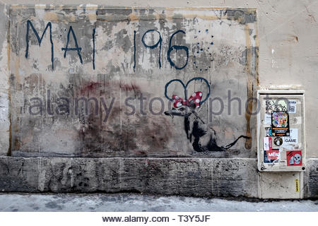 Street Art, A mouse carries the 8 of May 1968 like ears of Mickey (allusion to Euro Disney), a work of Banksy street Master Albert in the 5th district - Stock Photo
