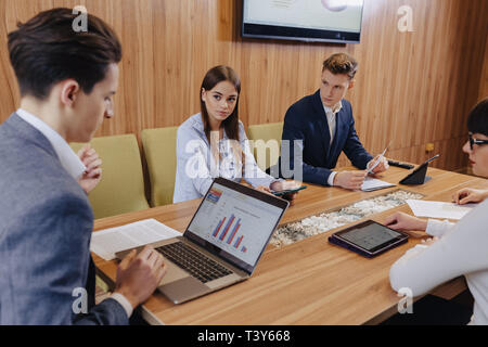 office workers like a team hold a meeting at one desk for laptops, tablets and papers, on the background a large TV set on a wooden wall - Stock Photo