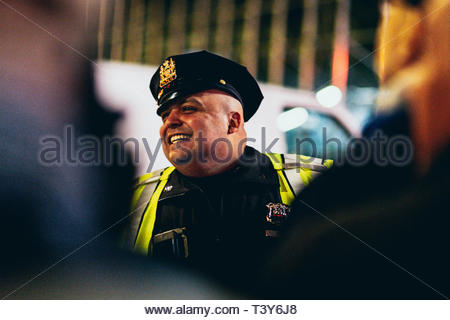 A police officer in charge of traffic smiles at Times Square for New Year celebrations. New York, December 29, 2018. Un policier en charge du trafic s - Stock Photo