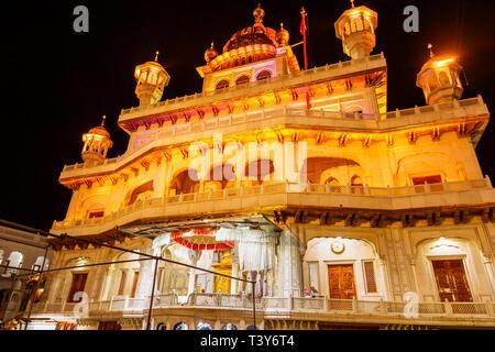 Sri Akal Takhat Sahib in the Golden Temple of Amritsar, the holiest pilgrimage site of Sikhism, Amritsar, Punjab, India, illuminated at night - Stock Photo