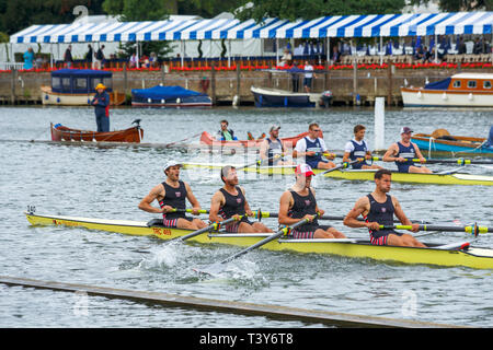 Two coxless four rowing boats and crews race to the finish line on the River Thames at Henley Royal Regatta, Henley on Thames, Oxfordshire, UK - Stock Photo