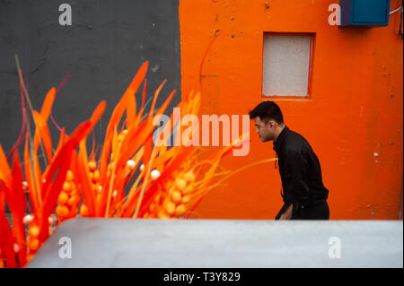 15.03.2019, Singapore, Republic of Singapore, Asia - A man is walking by an orange-coloured house wall in Singapore's Chinatown district. - Stock Photo