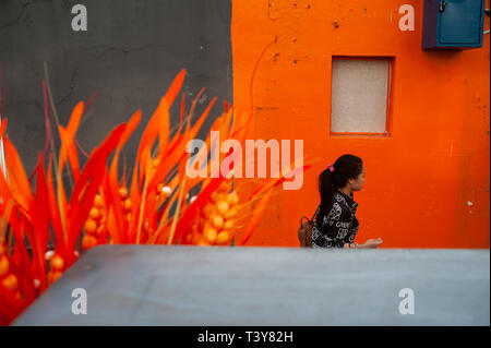 15.03.2019, Singapore, Republic of Singapore, Asia - A woman is walking by an orange-coloured house wall in Singapore's Chinatown district. - Stock Photo