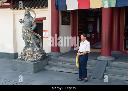 29.03.2019, Singapore, Republic of Singapore, Asia - A man is praying in front of the Buddha Tooth Relic Temple in Singapore's Chinatown district. - Stock Photo