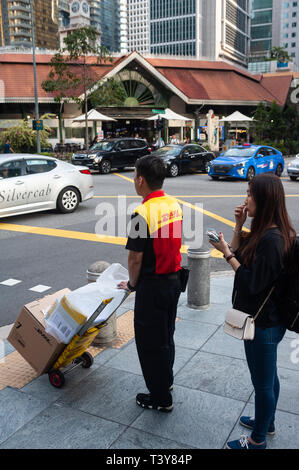 29.03.2019, Singapore, Republic of Singapore, Asia - A DHL delivery guy is waiting at a traffic light in the central business district. - Stock Photo