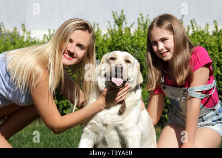 Family with a large Labrador Retriever in the background of a house on the lawn. Mother and daughter with pet sitting on the grass at the summer park. - Stock Photo