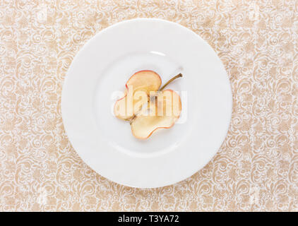 One thin slice of dried apple on round white plate in middle of  beige ornate patterned background. Healthy snack. Rigid diet concept. Top view, copy  - Stock Photo
