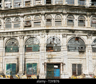 Facade of an old abandoned spanish trade building with power lines in front, in Escolta, Binondo, near the Pasig River, Manila, Philippines - Stock Photo
