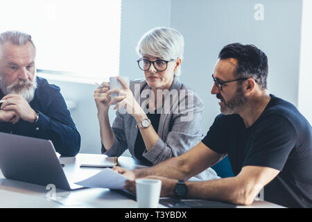 Business people talking while sitting at table in office. Businessman giving demonstrating on laptop to colleagues. - Stock Photo